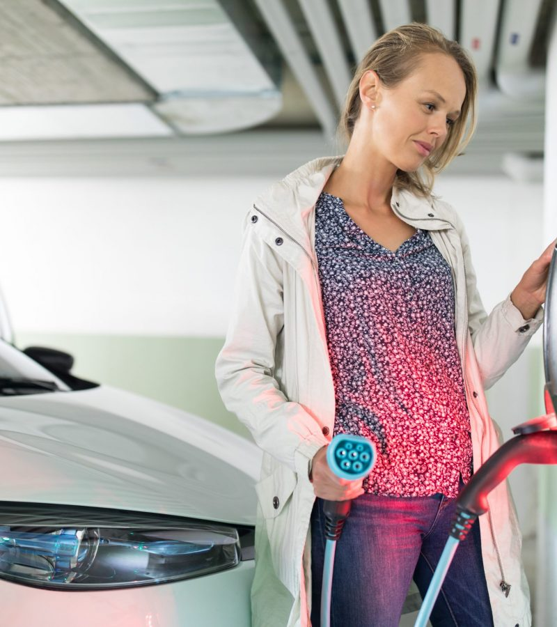 Young woman charging an electric vehicle in an underground garage equiped with e-car charger. Car sharing concept.